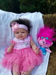 This Nov. 1, 2016 photo provided by Alisha John shows her daughter, Areea John, in Elton, La. John says her 3-month-old daughter has such a full head of hair that strangers stop to admire it, and she dressed the baby as a troll for Halloween. But John tells the American Press that she and her husband, Dakota John, don't have long to play with baby Areea's hair. That's because Dakota John is a member of the Coushatta Indian tribe, which shaves babies' heads as part of a blessing ceremony when they're four months old. (Alisha John via AP)