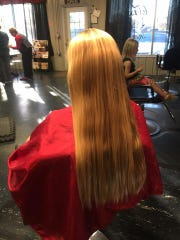 Thomas's long blonde locks before the cut. Thomas has donated her hair three times.