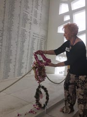 Charlene Sexton, of Estero, places a lei in honor of her father, Charles Mencer, at a memorial to the men who died aboard the USS Arizona in Pearl Harbor. While her father survived the attack, many of his friends died.