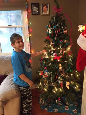 """Gina Migdal's son Benjamin puts the finishing touches on their """"Chanukah bush"""" this year. The family observes both Christmas and Chanukah."""