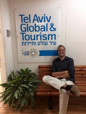 Austin Reid, a Lancaster native, sits in the Tel Aviv Global office during his summer internship.