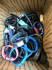 A box of used fitness trackers collected by RecycleHealth.