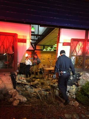 Police at the scene Tuesday at the Fowerville Farms Family Restaurant after an SUV crashed through the wall.