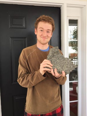 Caleb McMahon holds a piece of concrete that sent him to the hospital Monday after it fell into his vehicle but apparently caused no lasting injuries.