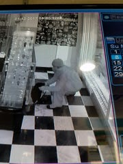 A burglar removes jewelry from a glass display case