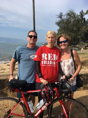 The parents of Sgt. Adam Schoeller, one of the marines killed in January 2016 off the coast of Oahu, with Patricia Waiwood, 27, who completed a 1,000-mile bike trek around the island on Saturday, the one-year anniversary of the crash.
