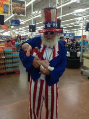 Ken Emerick, a former greeter at the South Hanover Walmart, poses with customer Daytona Duncan's daughter Lola on her first Fourth of July. Duncan said she went in the store just to see Emerick, who frequently dressed up on holidays. Emerick said he was fired following an incident this week.