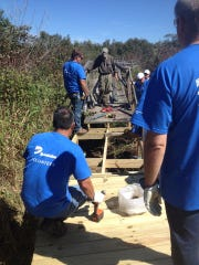 A crew of volunteers renovating a boardwalk trail at Woodland Dunes Nature Center and Preserve in Two Rivers.