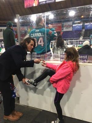 Mudbugs defenseman Dominick Procopio signs the shoe of 9-year-old fan Alyssa Hagedorn.