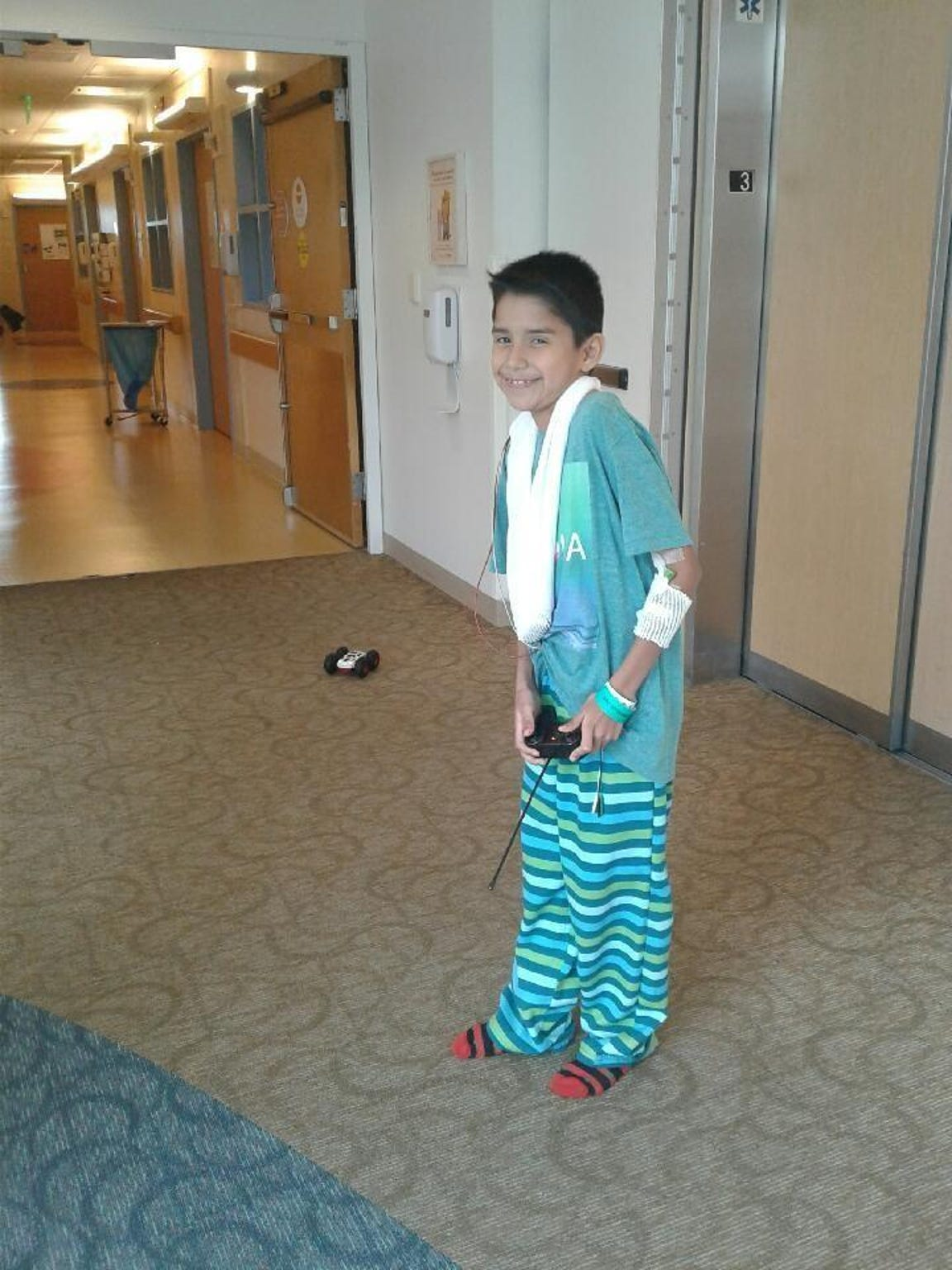 Isaac Guajardo, Jr., playing with a remote control car in the hospital hallway.