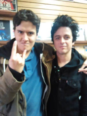 Diehard Green Day fan Alex Barnes of Green Bay, left, was thrilled to get a photo taken with lead singer Billie Joe Armstrong while he was shopping at The Exclusive Co. last week.
