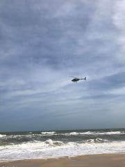 A helicopter scours the choppy waters off St. George Island for a missing swimmer Sunday.