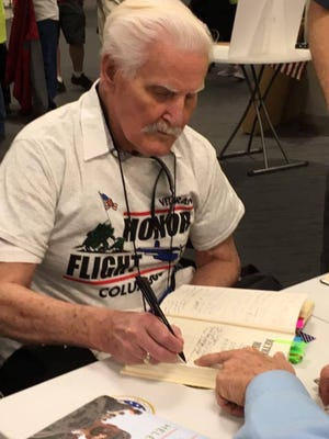 Norm Gerster signing a document during his April Honor Flight to Washington D.C.