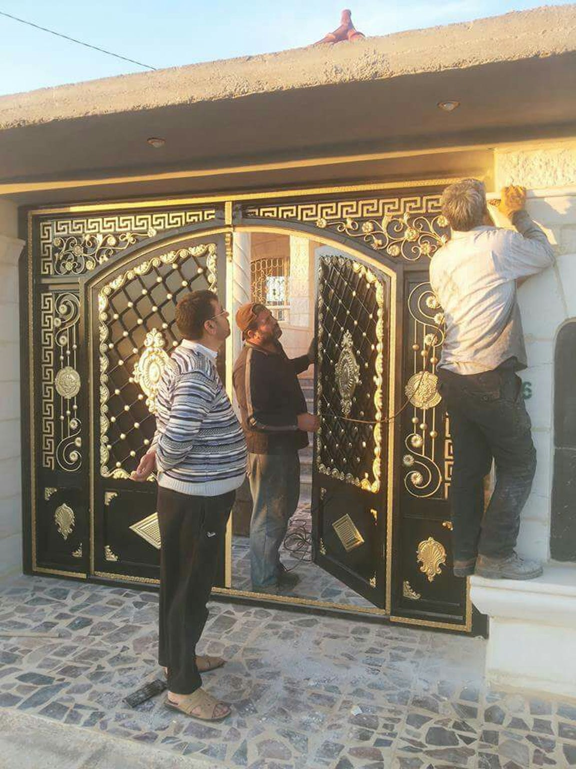 Abdul Mehsen Almasri, middle, works on a gold color-plated