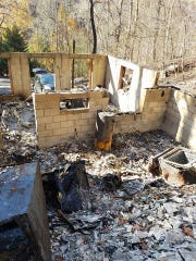 The remains of Chris Dunaway's cabin on Baskins Creek Road after the Nov. 28 wildfire. He recovered a metal container holding his mother's cremated remains in the living room area when he returned.