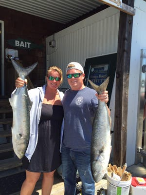 Jules and Billy Mister hold bluefish that they caught at the Cape Henlopen State Park fishing pier.