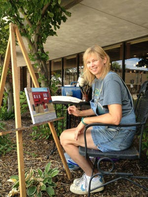 Kathryn Dreifeurst paints the view from outside her gallery windows in downtown Fond du Lac.