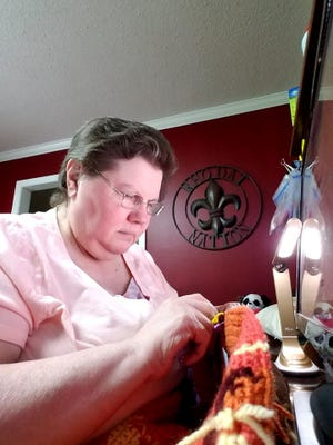 Delia McLaughlin multitasks crocheting and watching Facebook.