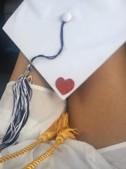 Gabby Satryb sits with her graduation cap in her lap, with a red heart sticker to remember her deceased mother by.