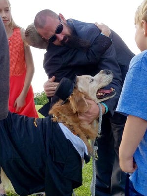 Tim Griffin gets a hug from his son, Elliot, and his dog, Mr. Molson, as his daughter, Chloe, looks on after Molson's wedding ceremony. Griffin and his children are embarking on dozens of adventures as they work through Molson's bucket list.