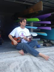 Chad plays ukulele in front of his garage full of adventure toys.