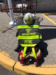 The turnout gear for Perth Amboy Fire Chief Abraham Pitre is on display in front the Perth Amboy Fire Department headquarters.