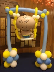 "A ""Baby in a Swing"" balloon sculpture was created by Britnie's Balloon Bonanza, owned by Britnie Davis."