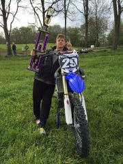 Andrew Povall poses with his motorcycle and a Motocross