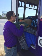A volunteer loads coats into the Code Purple bus on Monday during a drive put on by Chesapeake Utilities. The company sponsored a drive within all of their offices in the Delmarva area.