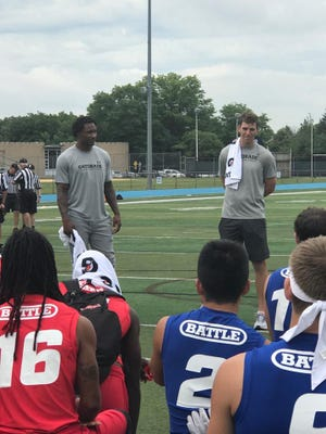 Giants quarterback Eli Manning (right) and wide receiver Brandon Marshall speaking to players at Wayne Valley's 7-on-7 tournament.