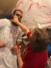Kristin Woller adds a layer of fake blood to Luke Stenberg's zombie makeup. The two practiced for the Haunted Sawmill's return in August on July 6.