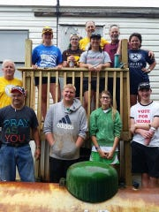 St. Michael Youth Mission workers and adult chaperones Les Shawver, John Asbrock, Michael Abele, Grace Fothergill, Alex Lambert on the ground, and Margaret Sharpshair, Isabel Dougherty, Isabel Baurmgartner, Emily Jansing, Ed Jansing, and Chuck Gibson on the new deck they built for the home during mission trip June 18-24.