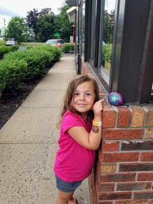 """Skylar Knaub, 4, of Hillsborough points to a hidden rock. Playing hide-and-seek with hand-painted rocks has become this summer's """"big thing."""" Community group members decorate and hide rocks around towns — in safe, public spots — for others to find and rehide. #HillsboroughROCKS"""