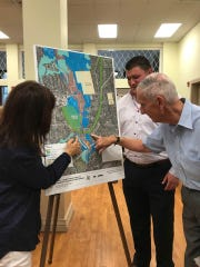 Little Falls Councilmembers Maria Cordonnier and Bill Liess, and Little Falls Mayor James Damiano, center, look at a diagram for the proposed footbridge that would connect the Peckman Preserve Trail to Wilmore Road/Memorial Park.