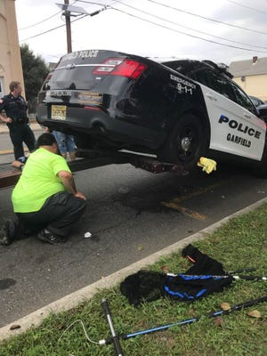 Garfield Police officer Noah Murphy helped rescue a cat that was stuck in the car axle.