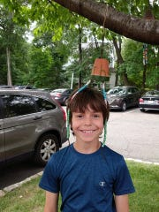 Ethan Jacobs with his wind chime on the library's lawn,