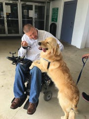 Cody Joss meets his new service dog, Mack, in May at