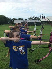 Members of the Holly Grove archery team practice their