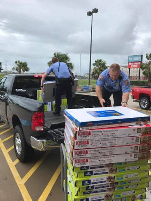 Police officers from Galveston, Texas, help the Humane Society of the United States unload crates to be used for pets displaced by Hurricane Harvey. The HSUS bought out an entire pet store's worth of crates for the effort.