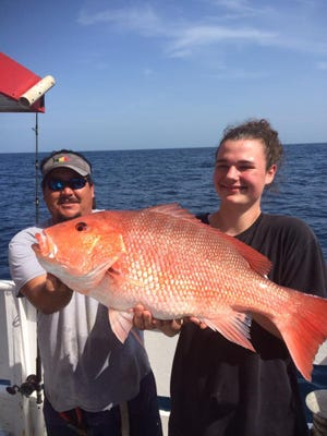 Mike Hsu, left, of Port St. Lucie, mate aboard Fort Pierce Lady, fishing daily out of Fort Pierce City Marina, helped this angler release a 20-pound genuine red snapper Tuesday aboard the boat.