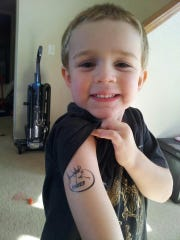 A 3-year-old Cayden Holmes shows off a temporary tattoo bearing the Rocky Mountain Elk Foundation logo.