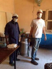 Nate Zimdars pasteurizes milk with his friend, Ibou,
