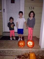 The Braatz kids show off their pumpkins, including the Packer one their dad carved.