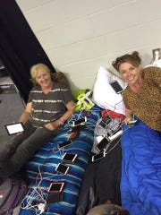 Patricia Fay and Anica Sturdivant power up a dozen or so devices for neighbors at Germain Arena