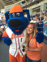 Laurie K. Blandford takes a break from a New York Mets spring training game to take a photo with St. Lucie Mets mascot Slider.