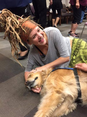 A woman cuddles with a comfort dog sent to Las Vegas after the mass shooting.