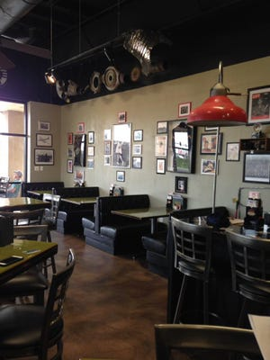 """Cafe B-29 encourages guests to bring in pictures of military veterans and those in active duty and place them on the """"In God we Trust"""" wall."""
