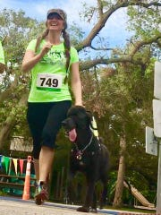 Jennifer Cleveland with her guide dog, Frank, at the Sprint for Sight 5K at Gleason Park.