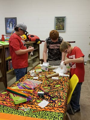 Children make mummies during a Halloween-themed event at Lumberton Public Library.
