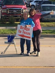 Jane Figal, right, and co-chair Jane Pushee direct drivers to the Grosse Ile Bridge to Texas charity drive on the island last month.